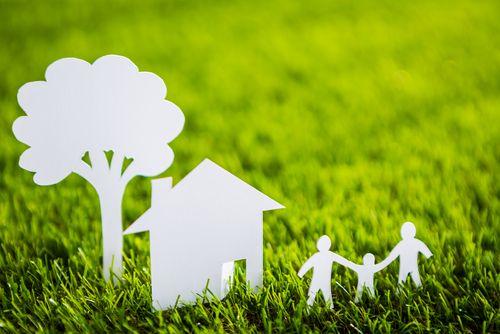 芝生の上に切り絵でできた木と家族
