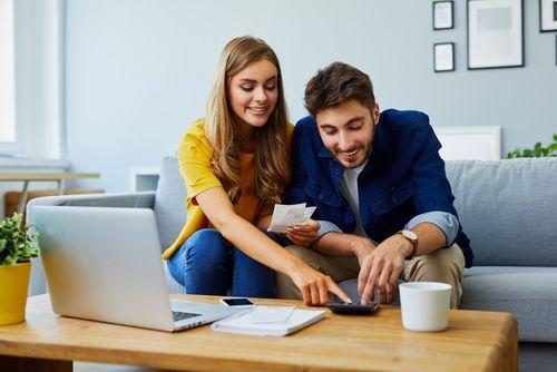 電卓で計算する笑顔の夫婦