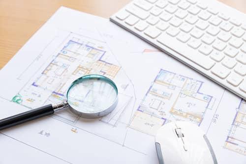 家の間取り図とパソコンと虫眼鏡