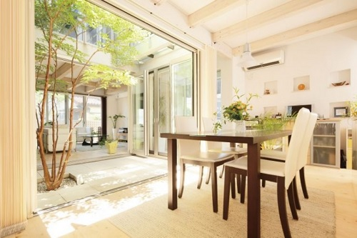 白いタイルを敷き詰めた中庭のある明るい家